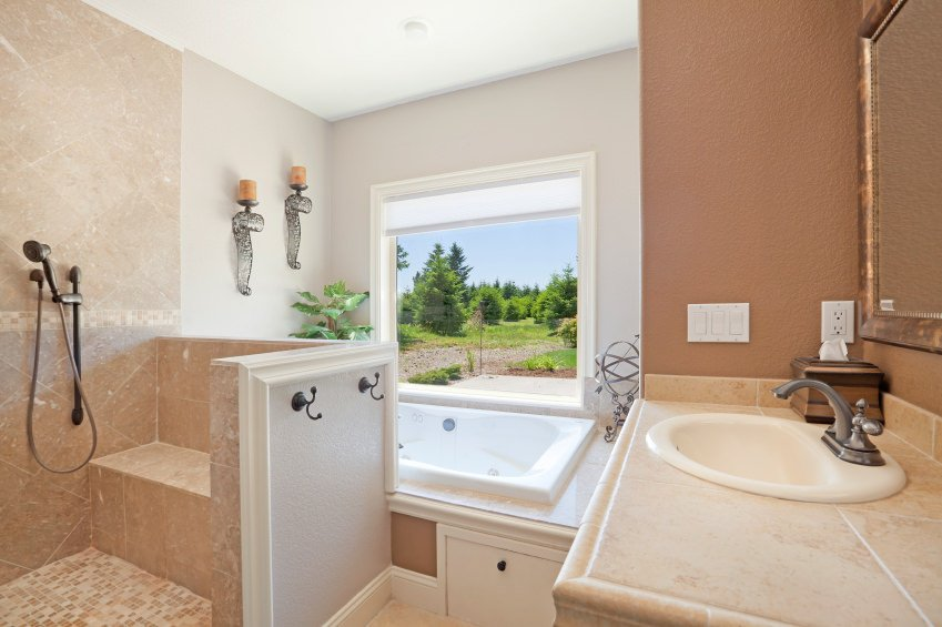 This primary bathroom boasts a corner bathtub near the window overlooking the beautiful outdoor area along with an open shower space.