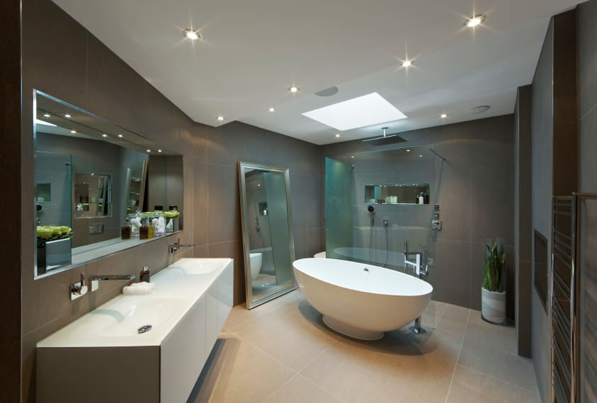 Modern and stylish primary bathroom boasting a skylight and recessed lights. The open shower looks very stylish. The freestanding tub matches with the white sink too.