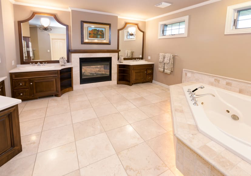 Spacious master bathroom featuring tiles flooring and gray walls. The bathroom offers a large drop-in tub, two sinks lighted by wall lights and a fireplace on the middle.