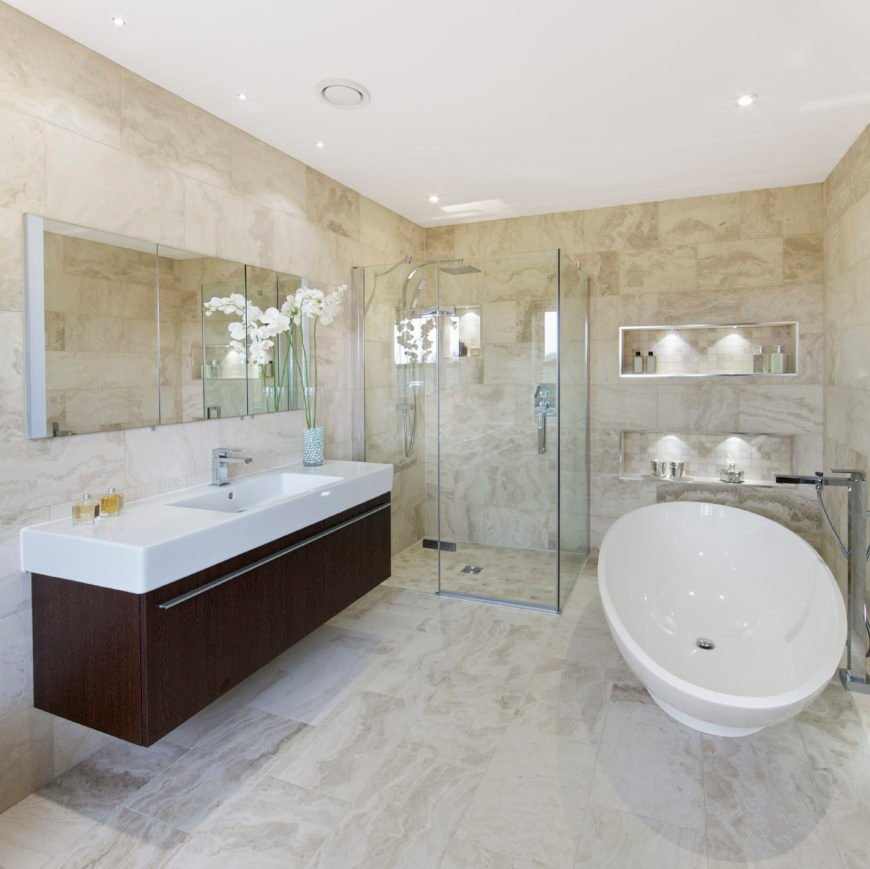 A master bathroom surrounded by stylish tiles walls and flooring. It also offers a freestanding tub and a walk-in shower, along with a floating vanity sink.