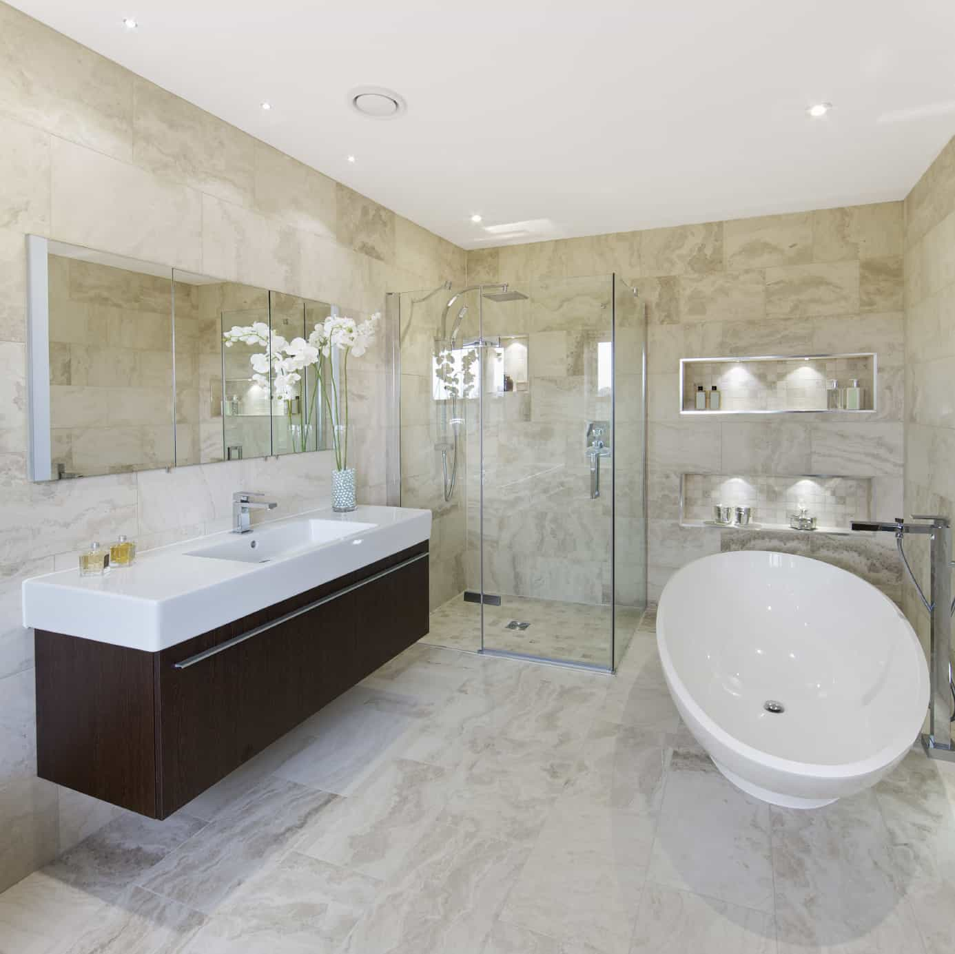 A primary bathroom surrounded by stylish tiles walls and flooring. It also offers a freestanding tub and a walk-in shower, along with a floating vanity sink.