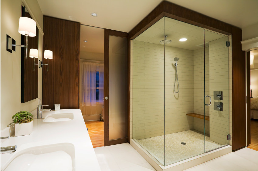 This master bathroom beside the master bedroom offers two sinks with white and smooth countertop and a walk-in shower room in the corner as well.