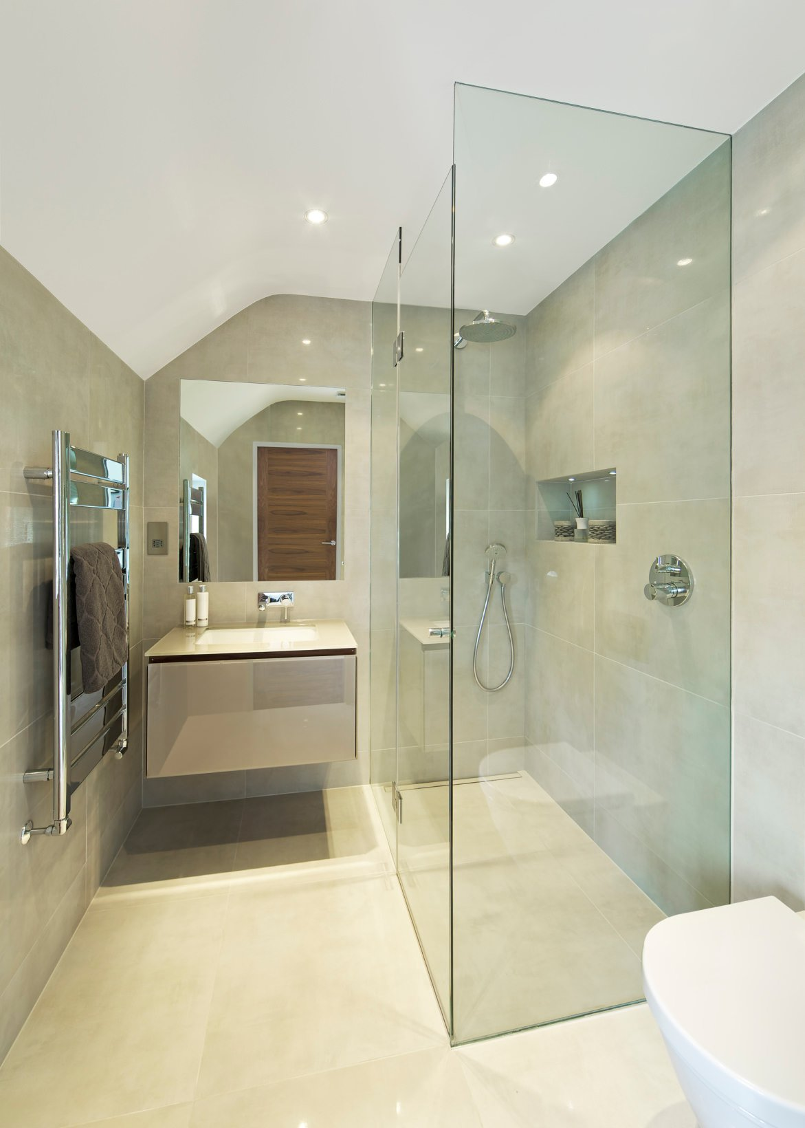 Frameless mirror and frameless shower cubicle make this bathroom look more spacious than it is. Add to it the neutral toned tiles and you have a stylish, fresh bathroom on your hands.