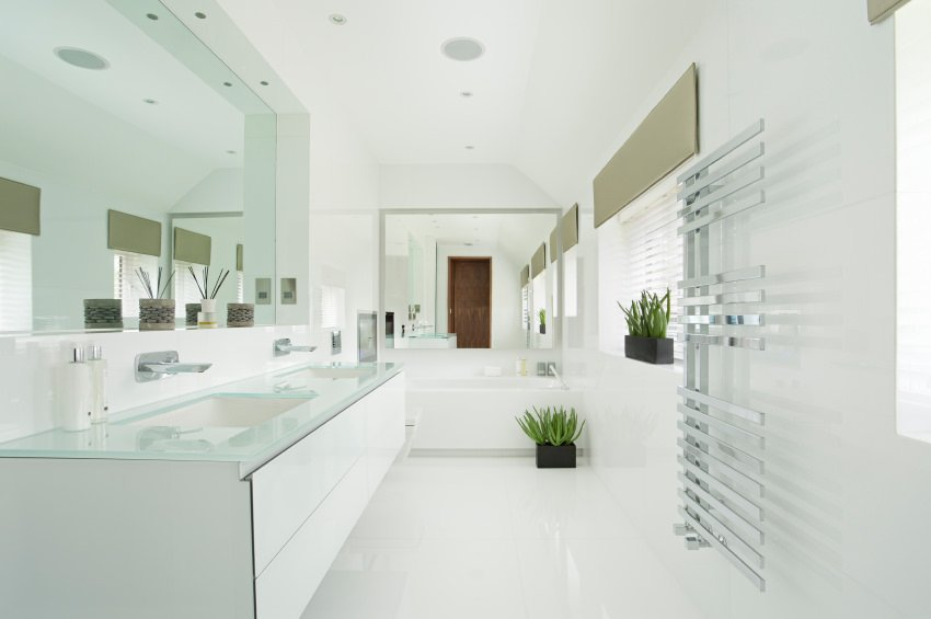 Bright primary bathroom with a stunning double sink surrounded by white walls and white flooring.