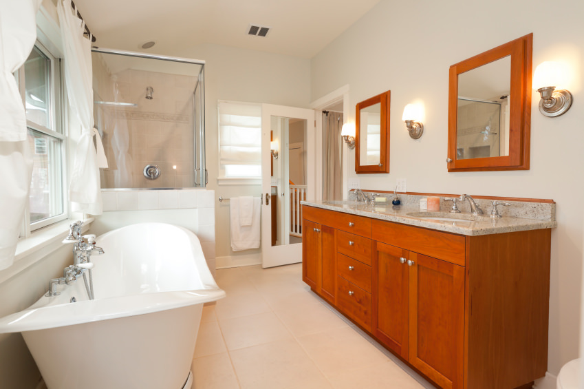 This master bathroom offers a nice looking soaking tub near the window and a walk-in shower in the corner. In front of the tub is the bathroom counter with two sinks and granite countertop.