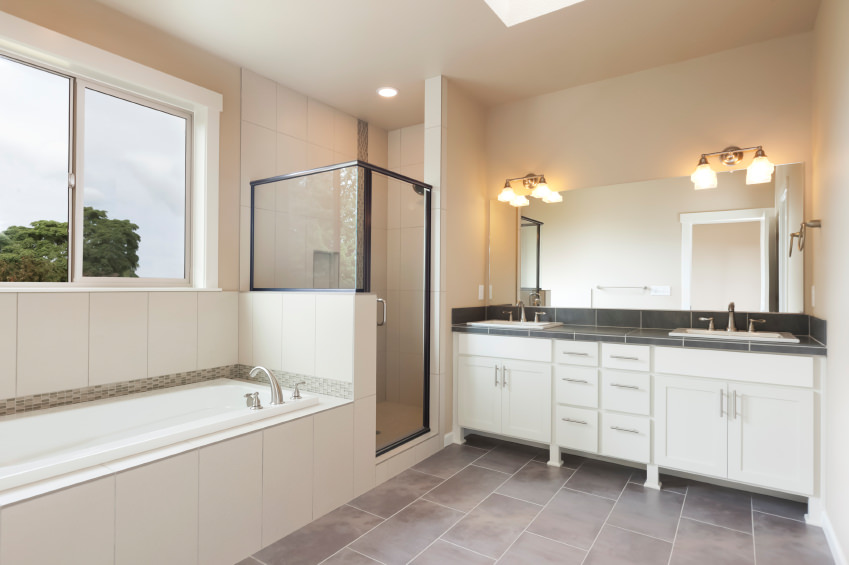 Large master bathroom with tiles floors and black tiles countertop. There are a bathtub and a corner shower, lighted by recessed lights and skylight.