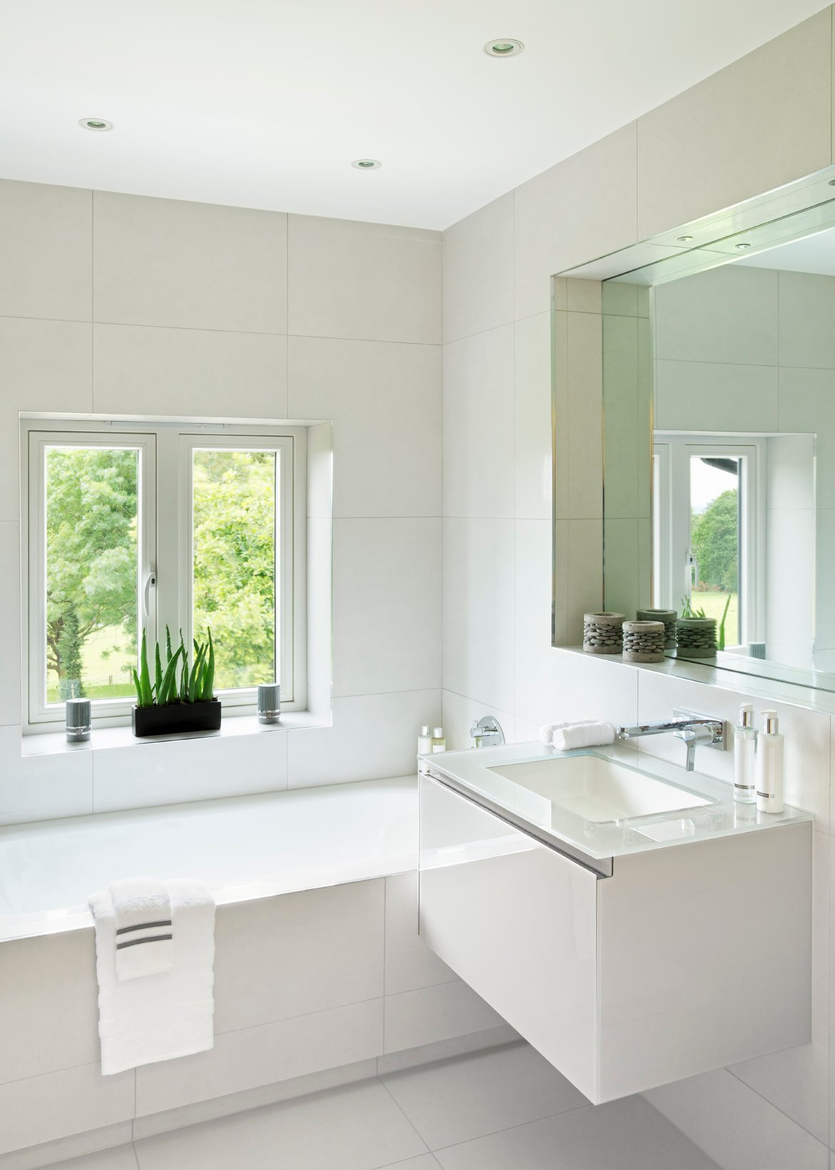 Giant oversized white colored tiles line the walls and flooring of this cube shaped bathroom and a large nook over the wall mounted contemporary styled vanity contains a large mirror and built in vanity lights. The large garden tub with sleek modern styled chrome fixtures with the translucent countertop and inset sink add finishing touches to this modern bright cube like bathroom.