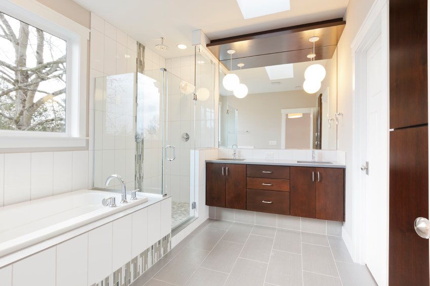 This master bathroom features a bathtub near the window and a walk-in shower in the corner lighted by pendant lights and a skylight.