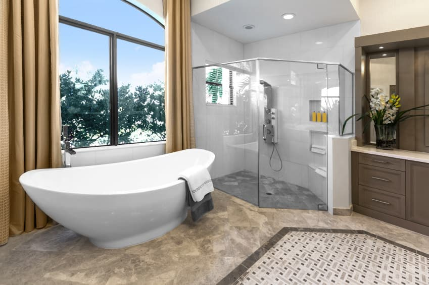 Modern primary bathroom boasting a stylish flooring, a freestanding tub and a walk-in shower area. The windows with brown curtains look perfect with the bathroom's style.