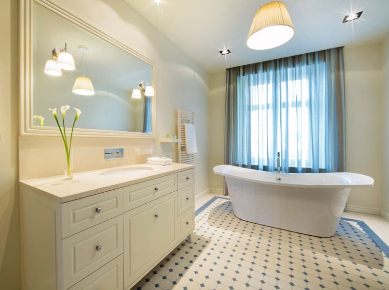 This beautiful master bathroom offers a cute rug. On top of it is the freestanding tub lighted by recessed lights and a pendant lighting.
