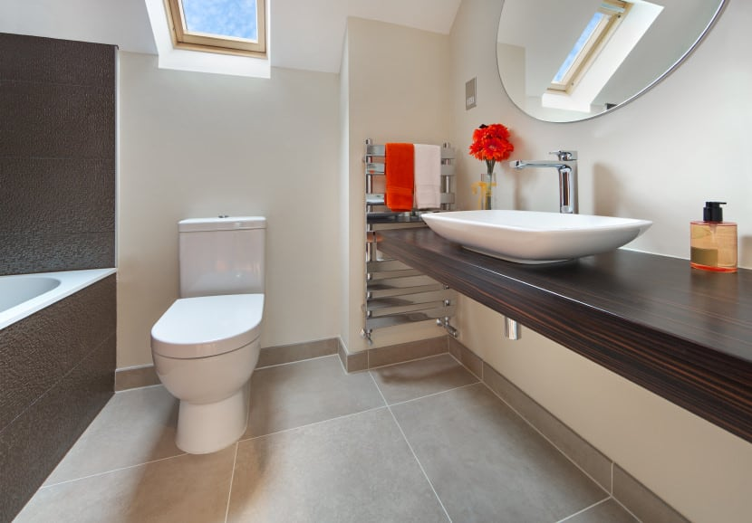This bathroom is equipped with a skylight to bring in extra light. It also has an extra long vanity table with a white, oval drop-in sink. An oval mirror hangs above the sink to add some depth to the room.