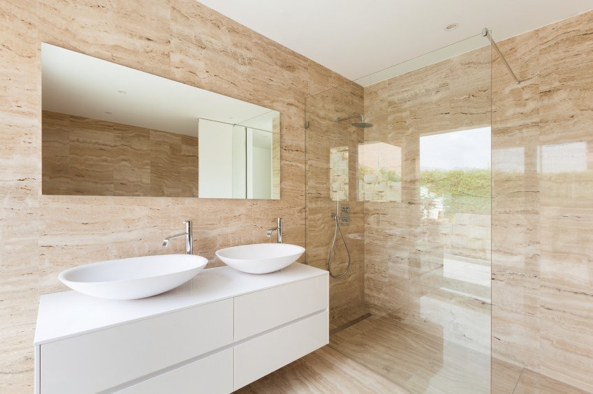 Primary bathroom featuring stylish walls surrounding the walk-in shower room and the two vessel sinks.