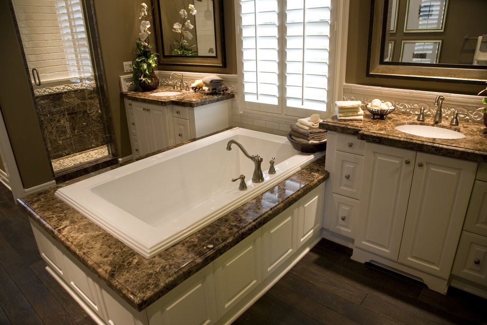 An elegant master bathroom with two-doorway shower area and a large deep soaking tub with a platform made of marble.
