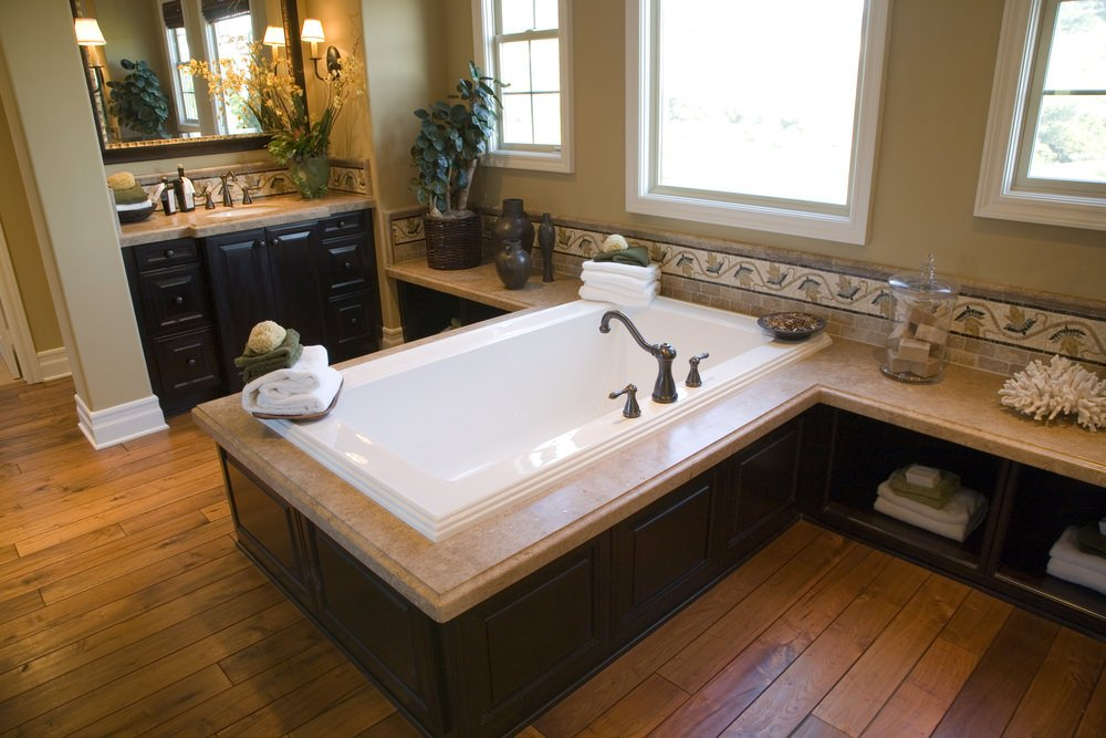 A focused shot at this master bathroom's drop-in tub with a classy platform. The room also features hardwood floors and beige walls.