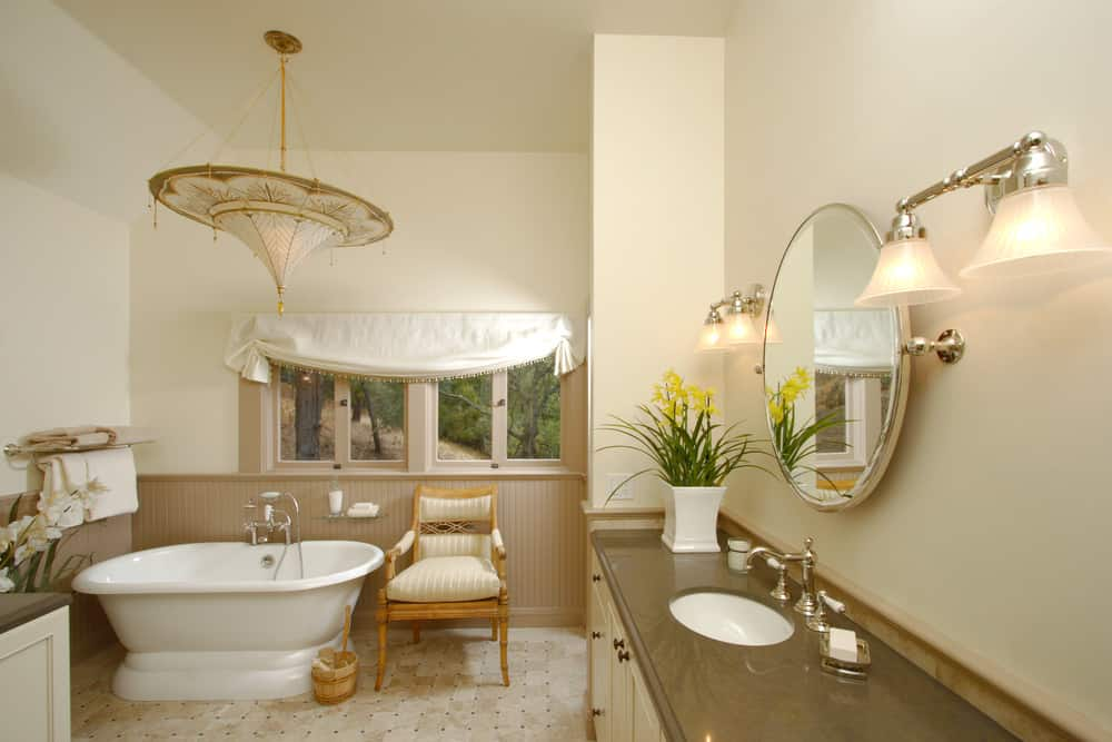 A classy master bathroom with a nice set of lighting. The flooring looks perfect with the kitchen's style. The freestanding tub is located near the window.