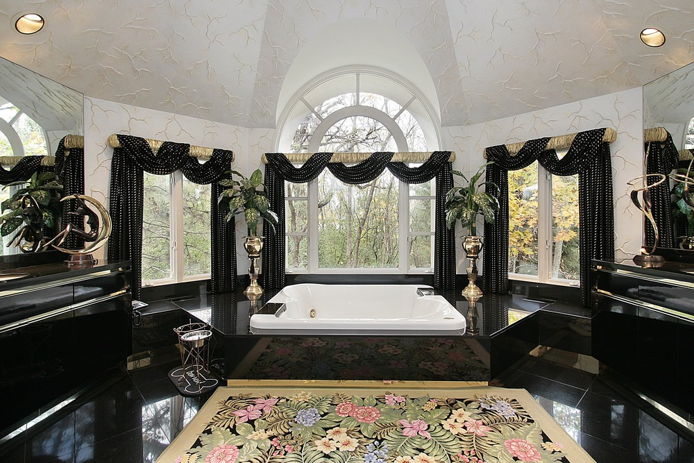 Primary bathroom boasting elegant black tiles flooring, sink counters and bathtub platform, along with black window curtains that look marvelous. The addition of the ceiling makes the room more stunning.