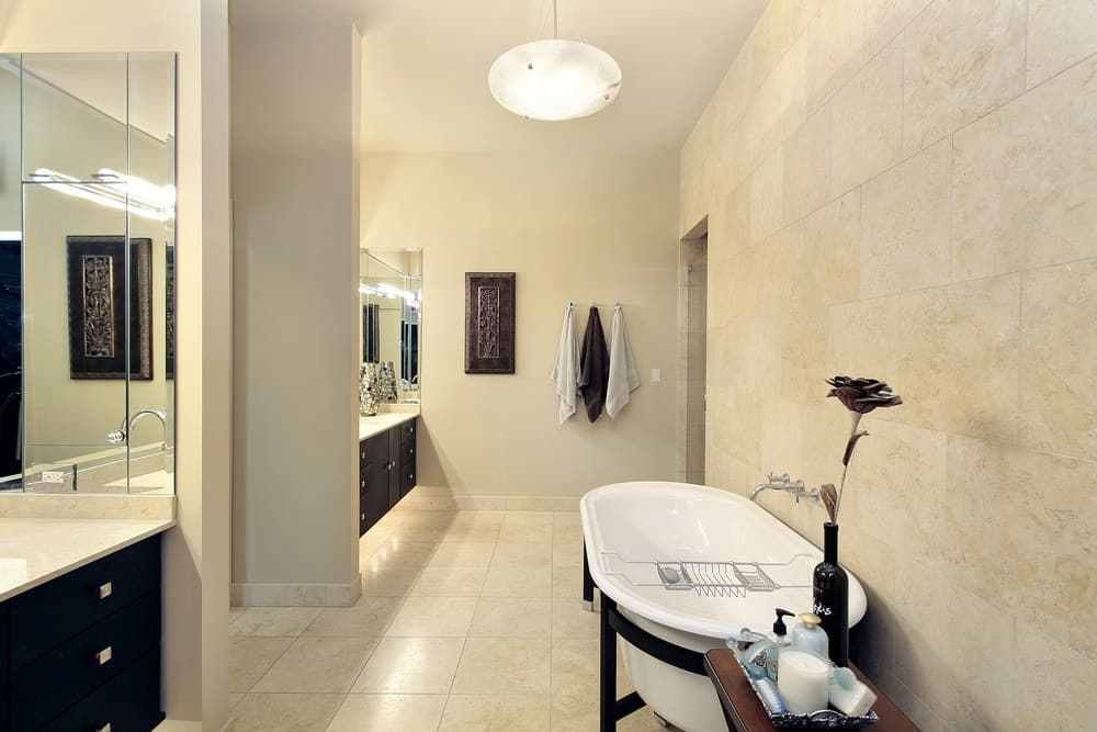 This master bathroom features beige walls matching the tiles flooring. The freestanding tub looks simple.