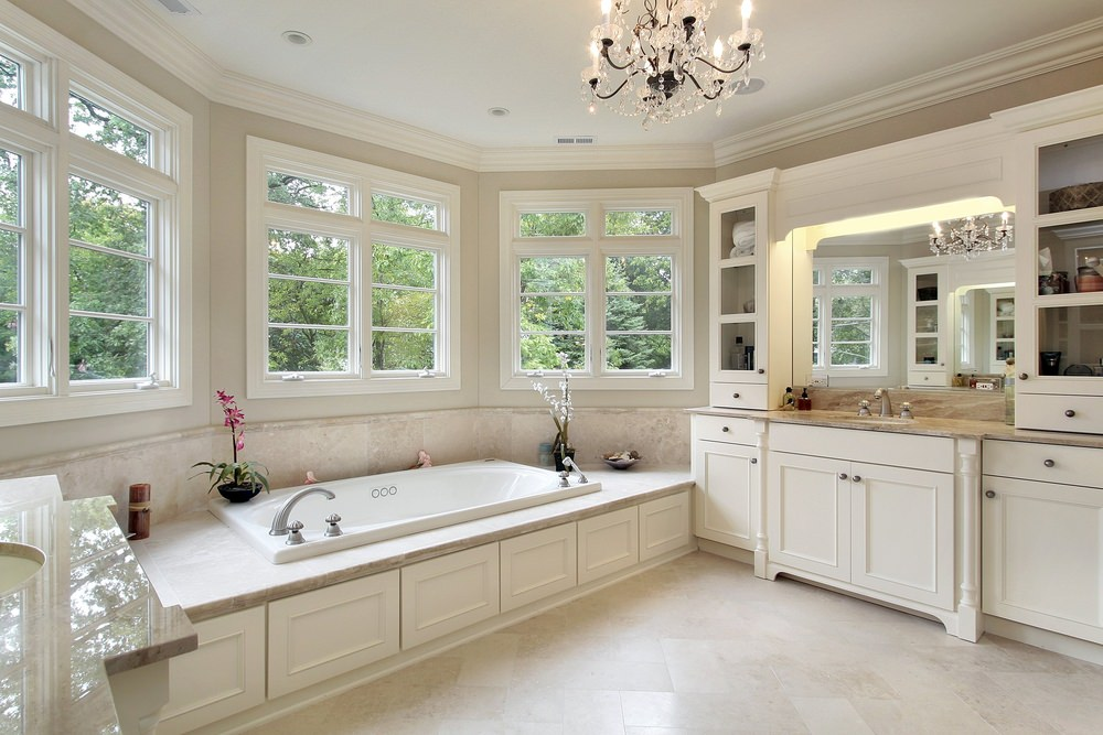 Primary bathroom featuring a deep soaking tub near the windows surrounded by gray walls and is lighted by a glamorous chandelier.