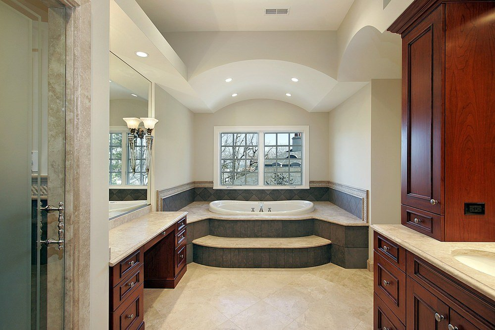 Primary bathroom featuring a drop-in tub with a handsome platform. It also features tiles floors and white walls.