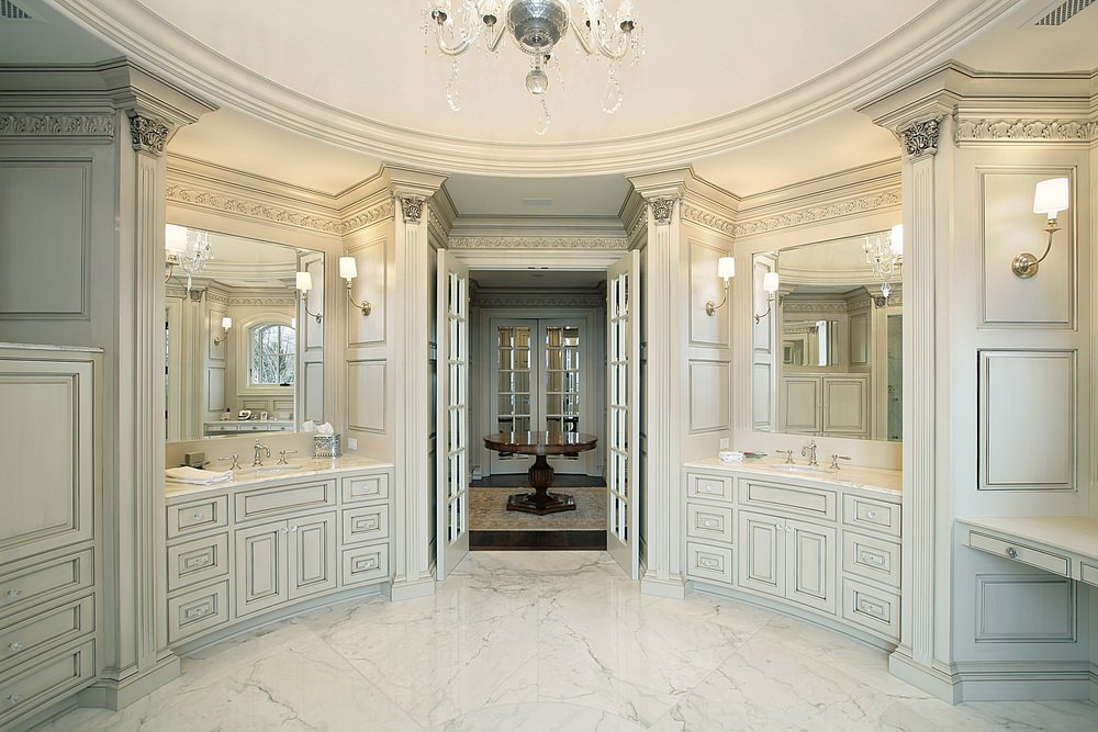 A primary bathroom with marble tiles flooring and marble sink counters lighted by wall lights. The room overall is lighted by a glamorous chandelier.