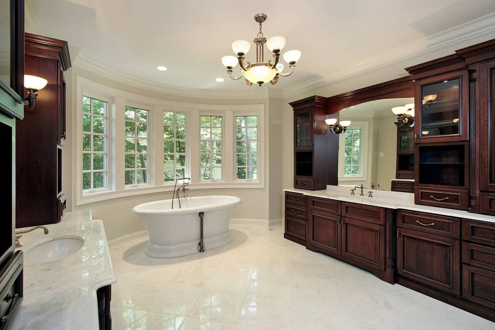 This primary bathroom offers a classy sink with a marble counter, a freestanding tub near the windows and is set on the tiles flooring and a ceiling lighted by a gorgeous ceiling lighting.