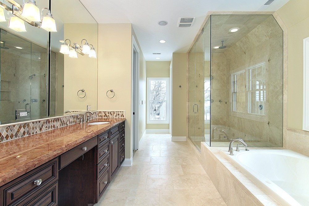 Primary bathroom featuring an elegant sink counter lighted by wall lights, a drop-in tub and a walk-in shower surrounded by beige walls.