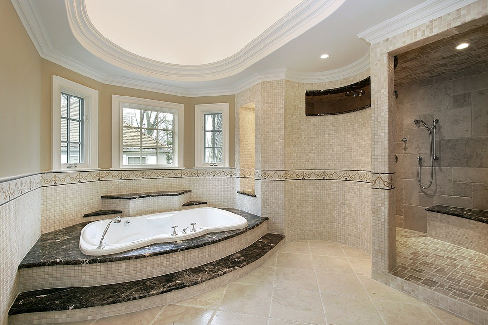 A primary bathroom featuring a stylish bathtub platform, a large walk-in shower room and a stunning white tray ceiling.