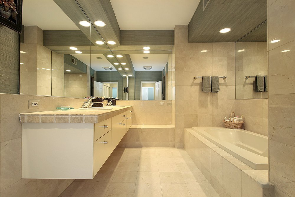 Primary bathroom with a drop-in tub on the side and a floating vanity with a double sink, surrounded by classy tiles walls and floors.