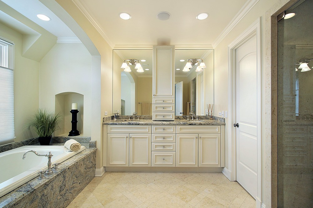 Large master bathroom with classy bathtub matching the countertop on both sinks. The pendant lights add glamour to the room.