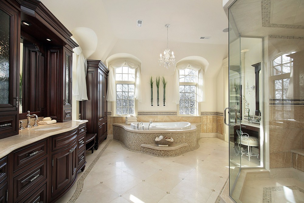 Primary bathroom with classy walls and ceiling lighted by an enchanting chandelier. The window curtains look lovely as well.