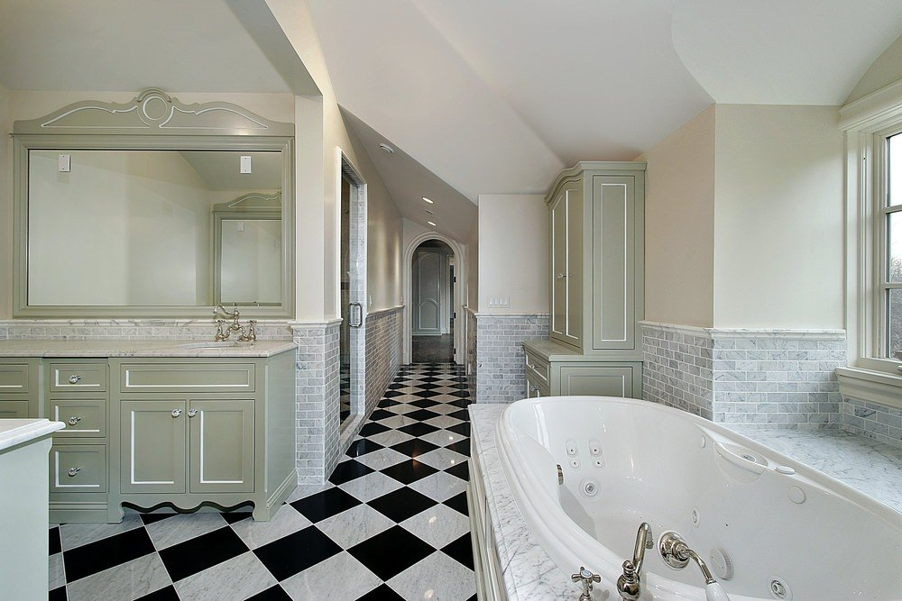 Large primary bathroom with stylish checker tiles flooring. It offers a large bathtub and a walk-in shower room.