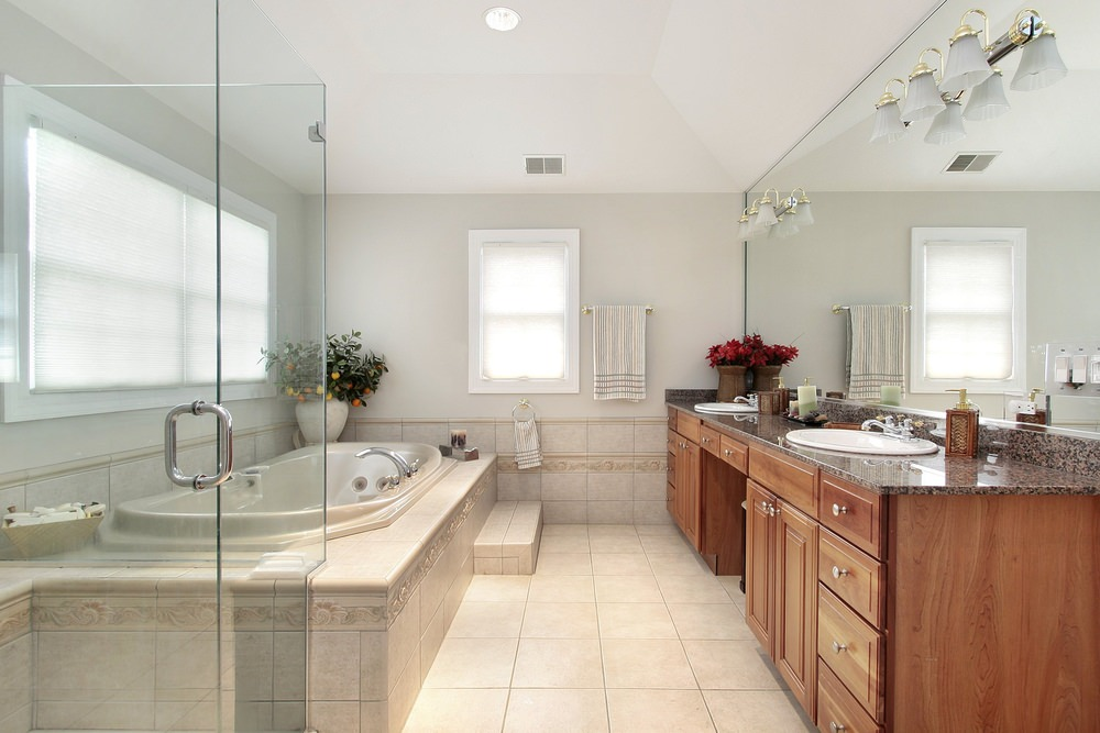This master bathroom features white walls and beige tiles flooring. The classy soaking tub looks elegant. On the side is the walk-in shower room. In front of the tub is the double sink lighted by wall lighting.
