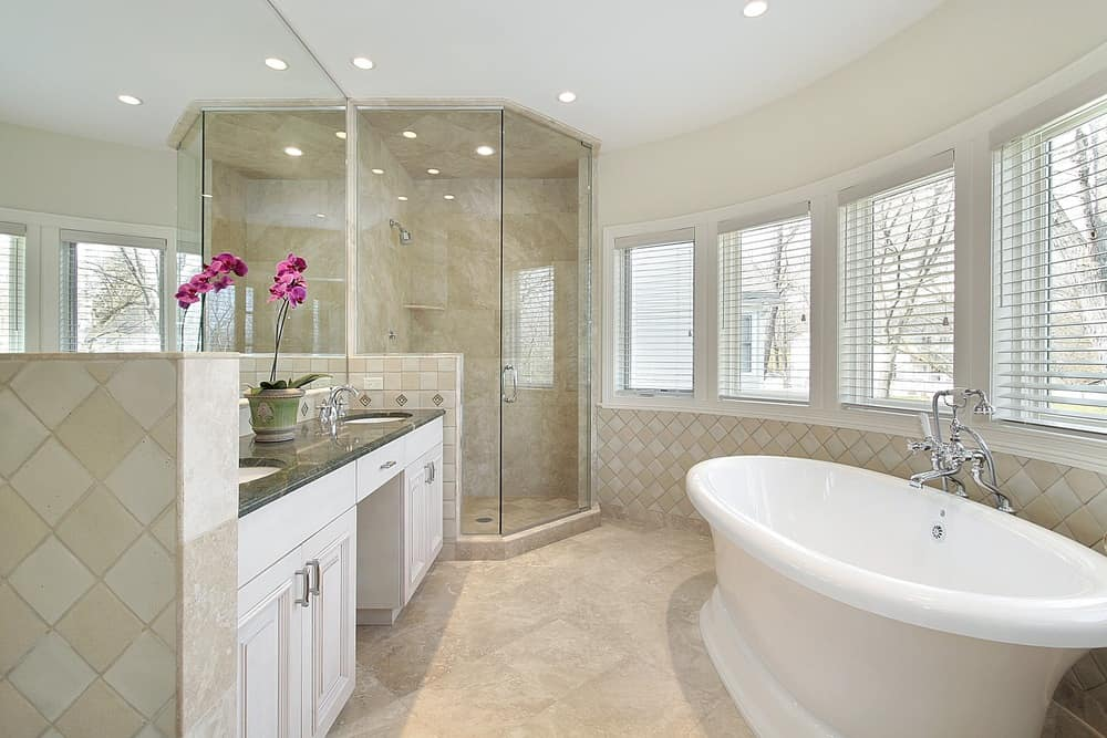 This primary bathroom features a walk-in shower and a freestanding tub near the windows. The sinks feature a granite countertop.