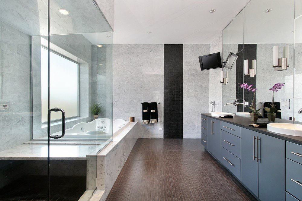 Large master bathroom featuring stylish tiles walls and hardwood flooring. The soaking tub looks absolutely glamorous while the bathroom counter with two vessel sinks looks stylish.