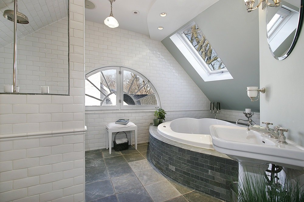 This primary bathroom boasts stylish tiles floors, a large bathtub and a pedestal sink.