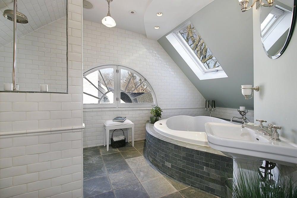 This primary bathroom boasts stylish tiles floors, a large bathtub and a pedestal sink.