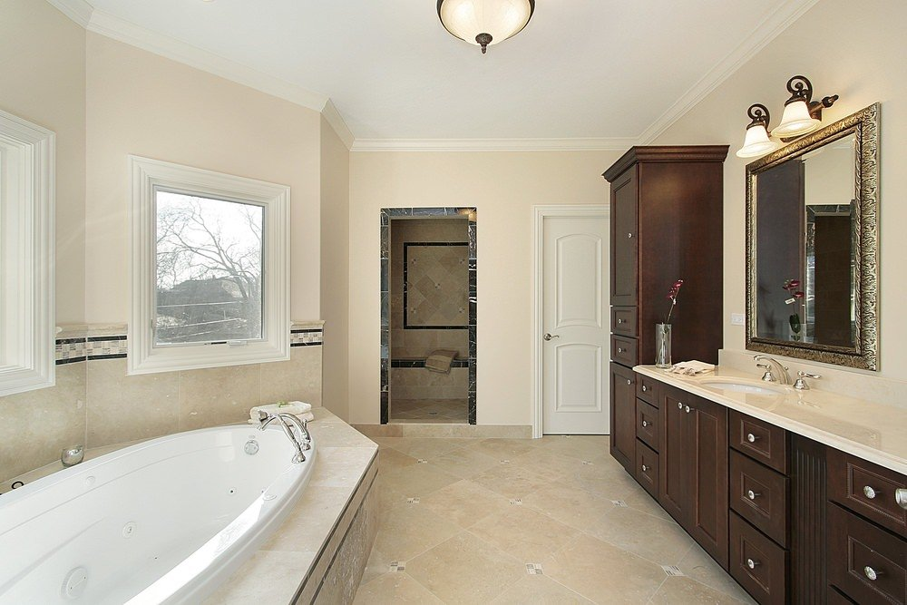 Primary bathroom with beige walls and tiles flooring. The sink counter features wall lighting. There's a walk-in shower and a deep soaking tub near the windows.