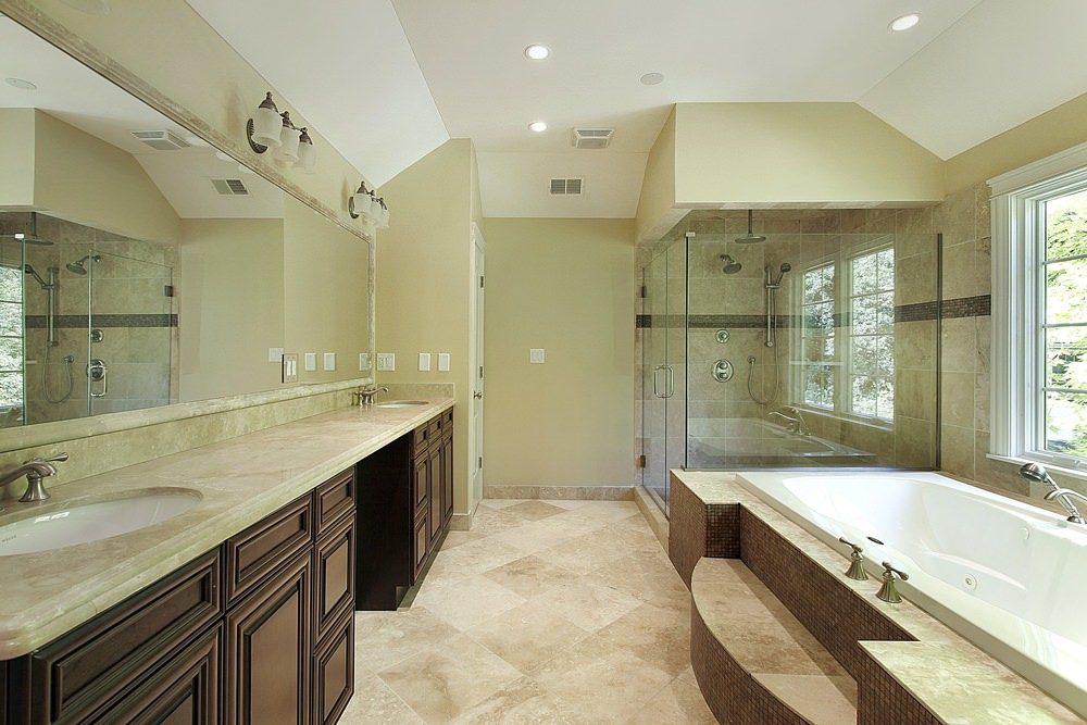 Primary bathroom featuring a long sink counter with two sinks and a marble countertop. It also has a deep soaking tub and a walk-in shower room.