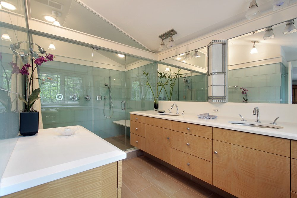 Large primary bathroom with a large walk-in shower along with a long counter with two sinks and a marble countertop.