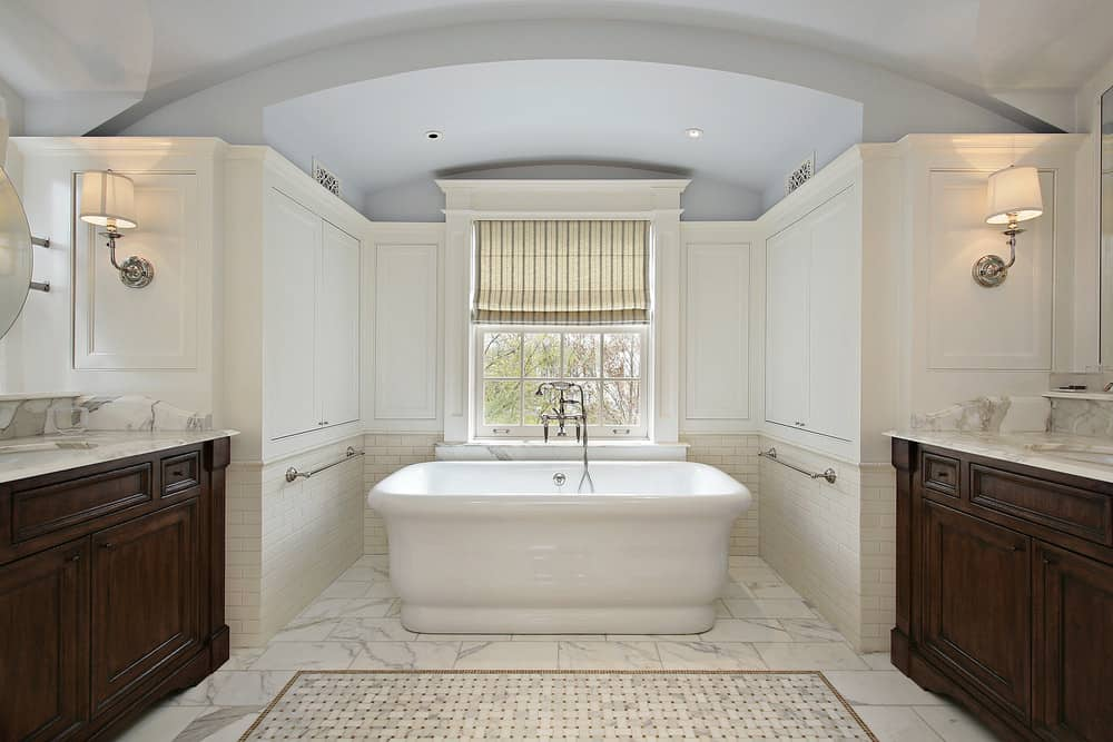 This primary bathroom has beautiful marble tiles flooring topped by a rug and a freestanding tub near the window.