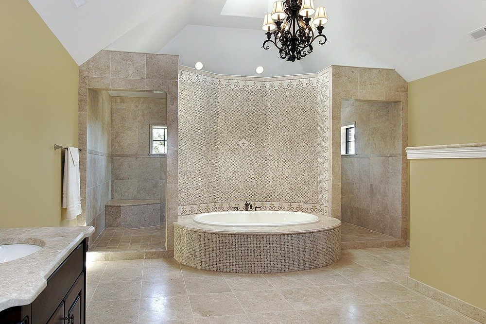 A master bathroom with a stunning wall and a bathtub platform. The room boasts a stylish chandelier.