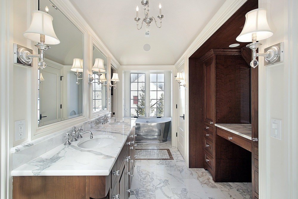 White primary bathroom with a double sink featuring marble countertop. There's a deep soaking tub on the corner as well. The room is lighted by wall lights.