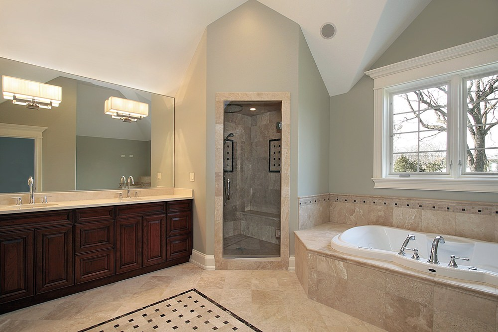 This master bathroom features tiles flooring and light gray walls, along with a double sink, a deep soaking tub and a walk-in shower room.