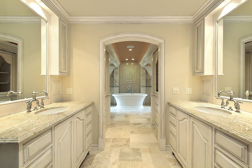 Master bathroom with a hallway featuring a cathedral ceiling leading to the elegant freestanding tub. The sinks boast marble countertops.