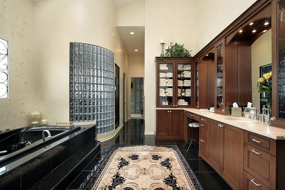 Master bathroom featuring elegant black tiles floors and black bathtub platform. The flooring is topped by a handsome rug.