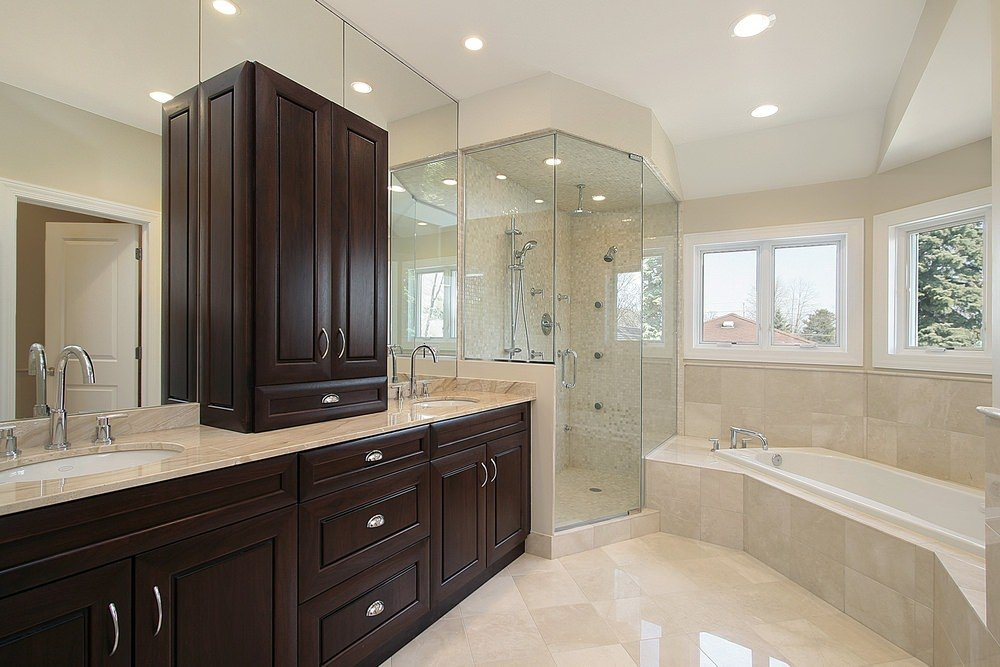 This master bathroom offers a stylish soaking tub and a walk-in shower in the corner. The two sinks with marble countertops look so gorgeous as well.