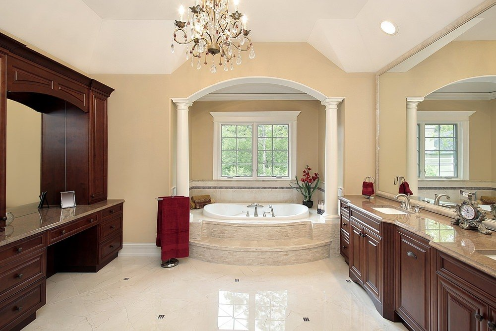 Master bathroom with beige walls, white tiles flooring and a tall ceiling lighted by a glamorous chandelier. There's a double sink and a powder counter.