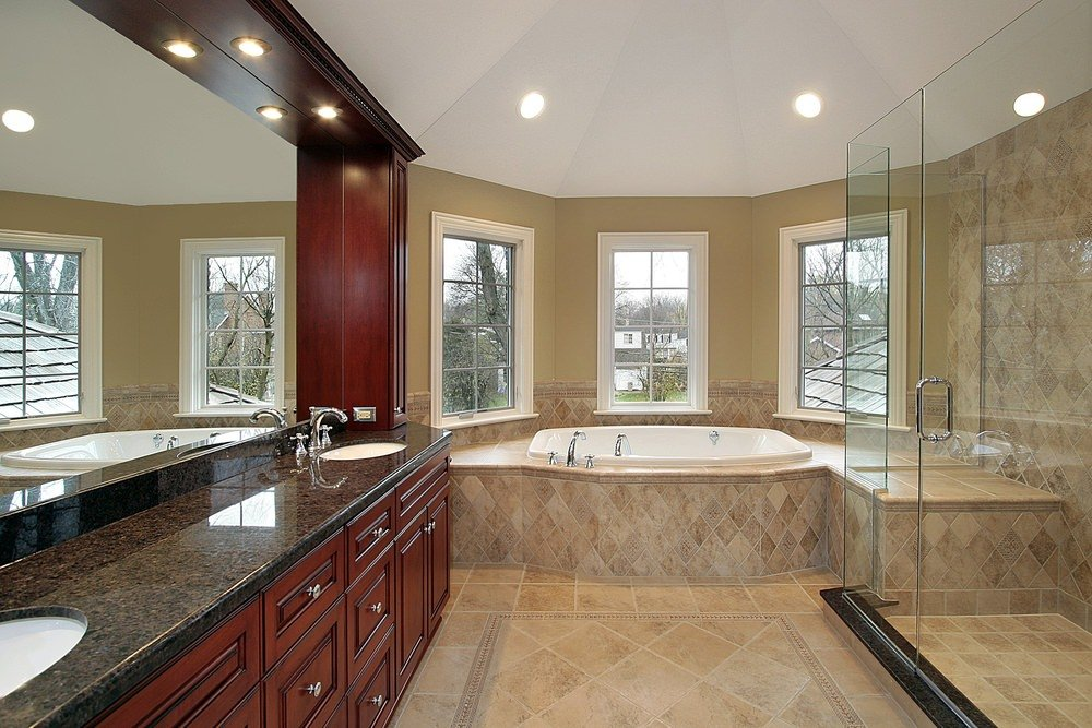 Master bathroom with black granite sink countertop, a deep soaking tub near the windows and a walk-in shower on the corner, lighted by recessed ceiling lights.