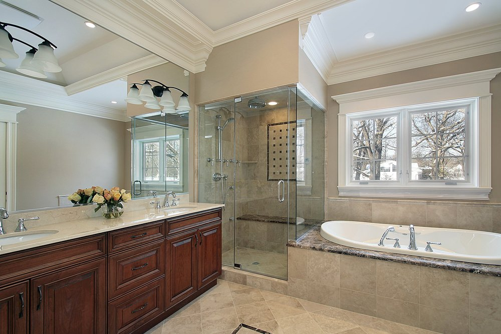 A master bathroom featuring tiles floors, a marble sink counter, a large bathtub and a walk-in shower room. The room also has a gorgeous white ceiling.