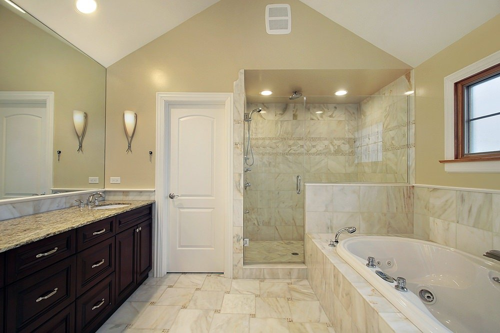 A master bathroom with a large deep soaking tub and a walk-in shower room. It also features tiles flooring and a  granite sink countertop.
